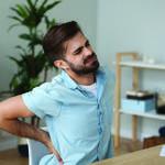 Tired man feeling pain in back suffering from lower backache