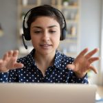 Person wearing headphones with hands up at computer screen