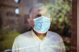 Older man wearing a COVID-19 mask staring out of the window