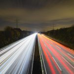 Long exposure shot of motorway car lights at night with trees and pylons