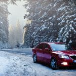 Red Skoda car driving through snowy forest road by fir trees