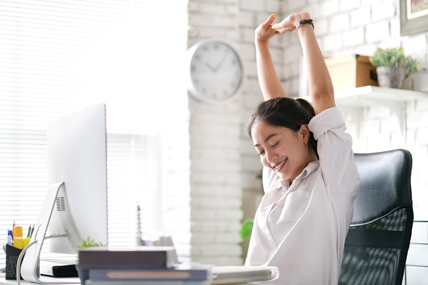 Lady stretching her arms above her head while sitting at her desk