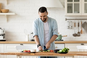 Man chopping food at the kitchen counter, eating for wellness